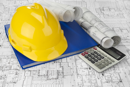 Yellow helmet, calculator, blue folder document and project drawings