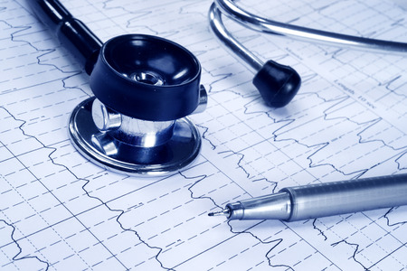 Stethoscope and technical pen on the cardiogram background