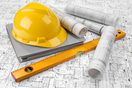 Yellow helmet, level, grey folder document and project drawings Stock Photo