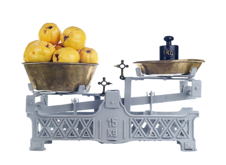 Old-fashioned balance scale with quinces isolated on white background