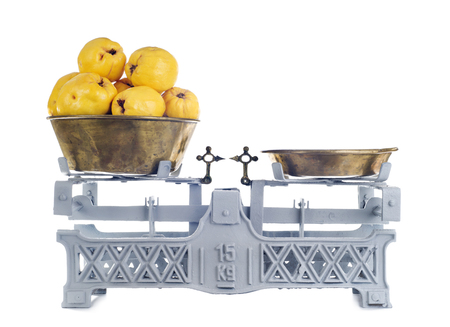 counterweight: Old-fashioned balance scale with quinces isolated on white background