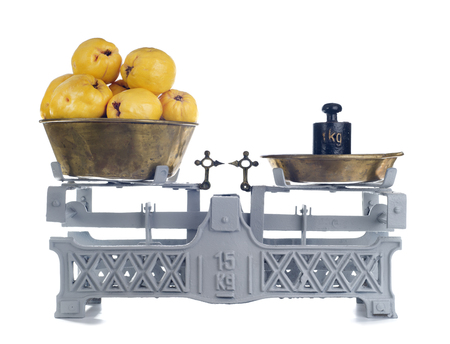counterpoise: Old-fashioned balance scale with quinces isolated on white background