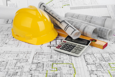 construction project: Yellow helmet, calculator, level and project drawings