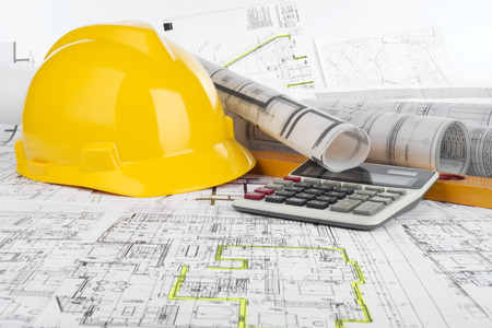 Yellow helmet, calculator, level and project drawings