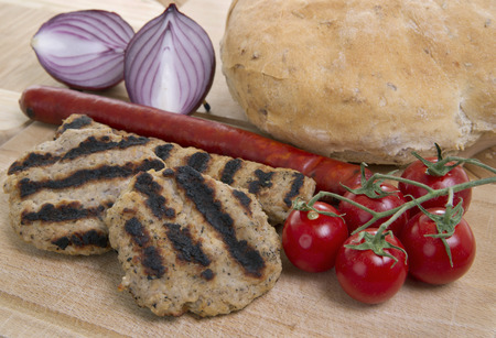grilled meatballs and sausage whit cherry tomatoes, bread and red onions on wooden platter Standard-Bild