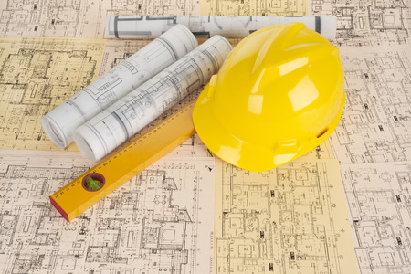 Yellow helmet, level and project drawings Standard-Bild