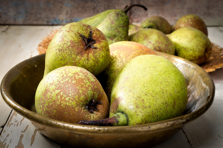 pears in copper tray on wooden table, selective focus Stock Photo