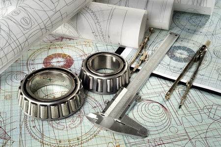 roller bearing, vernier callipers , compasses, clipboard and drawings, selective focus