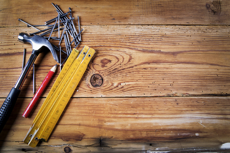 Nails, hammer,  pencil and folding meter on wooden background Stock Photo