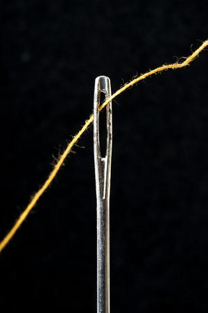 needle and thread on  black background Stock Photo
