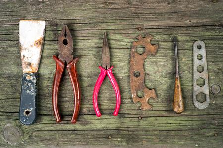 chave de fenda, pinças, chaves e paletes em fundo de madeira