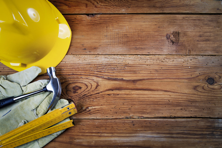 hammer, protective gloves, folding meter and yellow safety helmet on wooden background