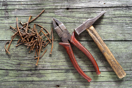 hammer, nails and nippers on wooden background