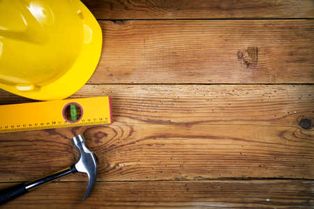 Yellow helmet, hammer and  level  on wooden background