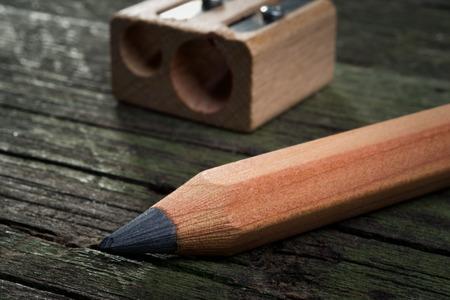 Lápis e apontador em fundo de madeira