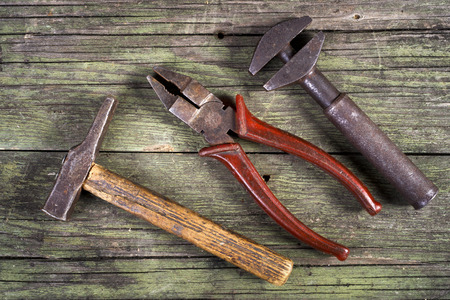hammer, nippers and wrench on wooden background