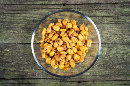 spiced fried corn in glass bowl on wooden background