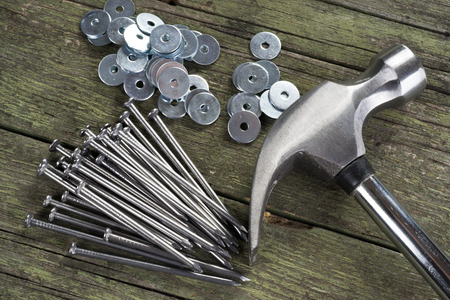 hammer,  nails and washers on wooden background