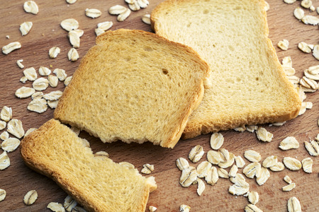 sliced bread and oat flakes on wooden table