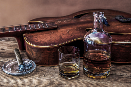bottle, glass of whiskey, cigar and old guitar