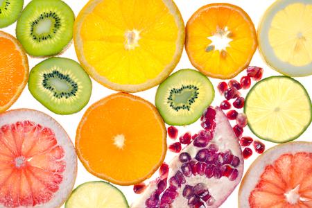 Fresh cut into circles citrus fruits, pomegranate and kiwi on white background