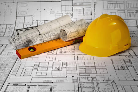 Yellow helmet, level and project drawings Standard-Bild - 99910668