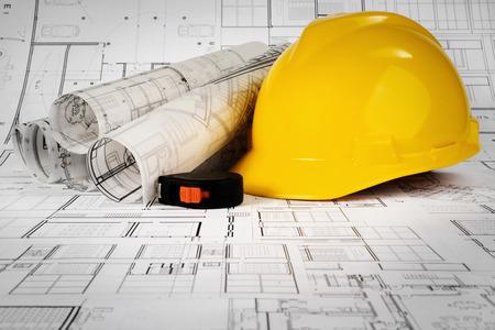 Yellow helmet, tape measure and project drawings Standard-Bild - 99972369