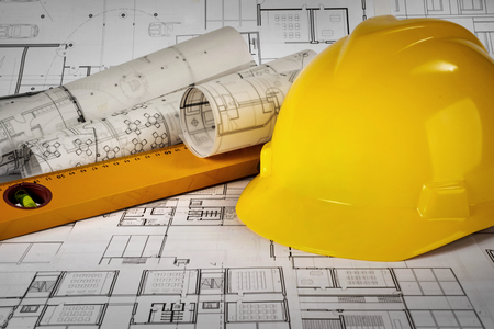 Yellow helmet, level and project drawings Standard-Bild - 99904224