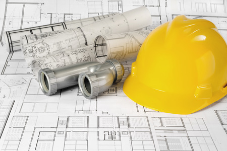 Yellow helmet, siphon and project drawings Standard-Bild - 99904225