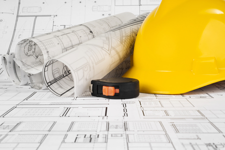Yellow helmet, tape measure and project drawings