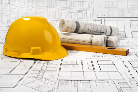 Yellow helmet, level and project drawings Standard-Bild - 99904228