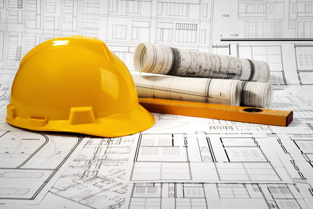 Yellow helmet, level and project drawings Standard-Bild - 99904231