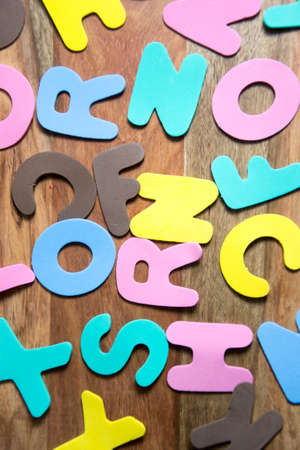 alphabetic character: colorful letters on wooden background Stock Photo