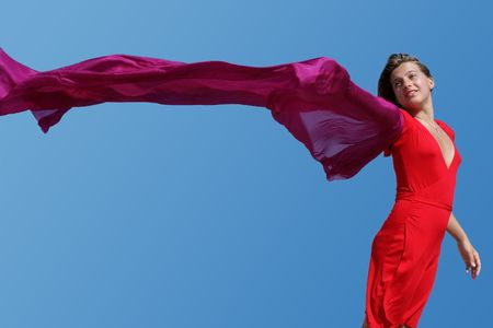 young women with red fluttering scarf on blue sky background photo