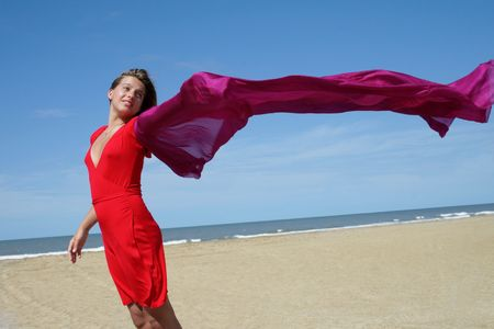young women in red dress on ocean beach with red scarf fluttering on wind photo