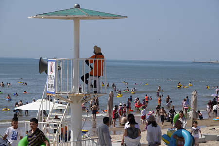 Lifeguard tower at beach with crowded people Editorial
