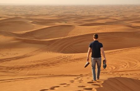 Man walking alone in the sunny desert near Dubai Stock Photo
