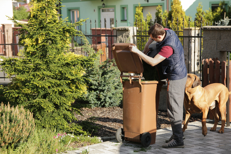 Adult man in the garden and filled grass clippings in the trash Stock Photo