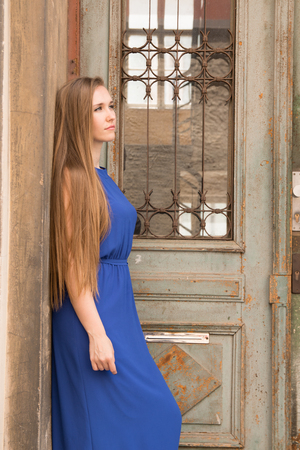 modest: Modest young girl on the background of the old wall with door Stock Photo