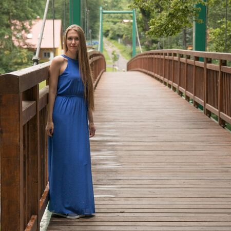 modest: Modest young girl on bridge and the green background of trees