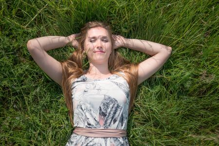 girl lying down: Portrait of a young girl lying down on grass in the park