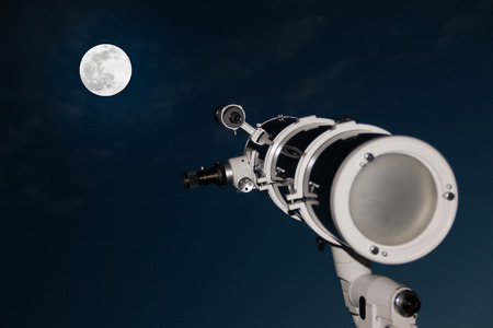 astrophoto: Astronomical telescope over dark sky with the moon in the night