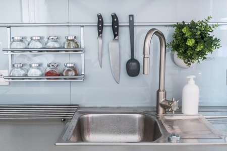 Modern kitchen in grey color at home with kitchenware