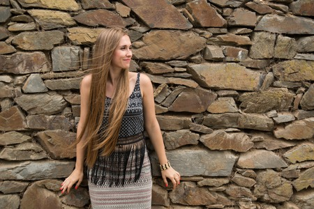 modest: Modest young woman on the background of the old stone wall
