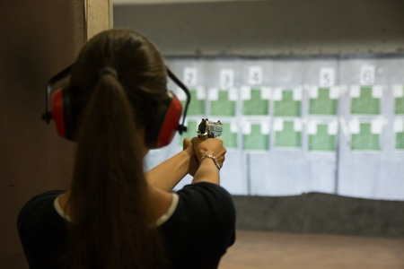 Woman is aiming a gun in the shooting-range in shooting gallery