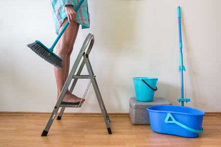 Young woman cleaning home with ladder, buckets and brush