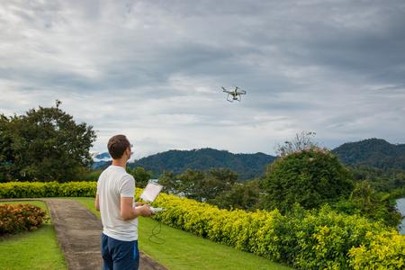 PHUKET, THAILAND - 8.11.2016: Man with remout controling drone DJI Phantom 4 in Phuket, Thailand