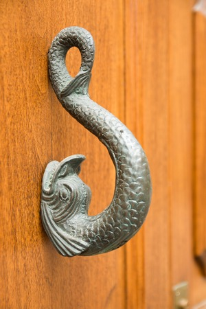 Old wooden door to house with a brass knocker in the shape of a fish