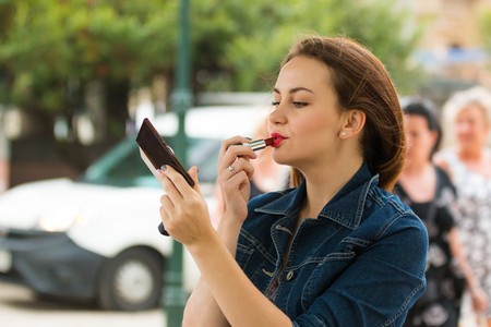 corrects: Woman corrects make-up by red lipstick in the park