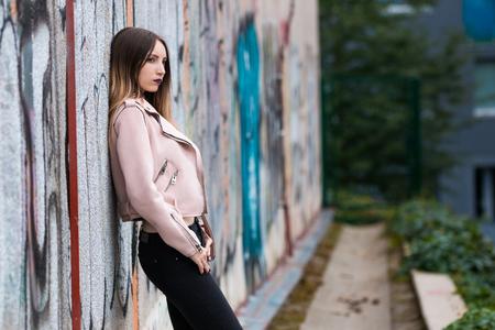 Portrait of informal fashionable girl on graffiti wall background Фото со стока